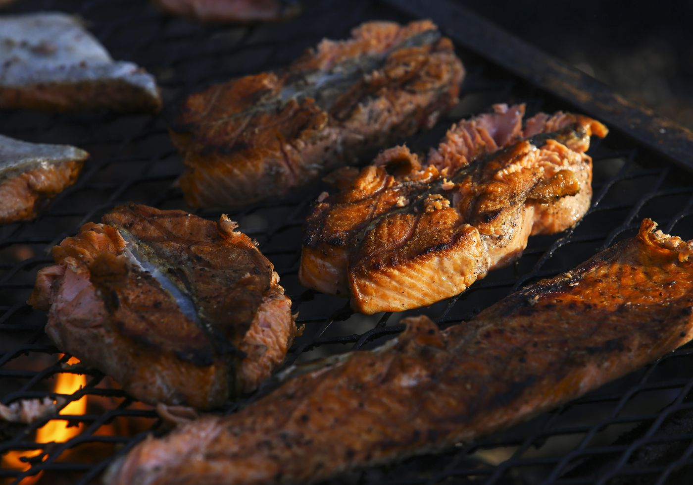 King salmon cooks over a flame on a grill at Hartney Bay in Cordova on Tuesday, May 18, 2021. The salmon was harvested by fisherman Matt Honkola the night before during the first Copper River opener of the season. (Emily Mesner / ADN)