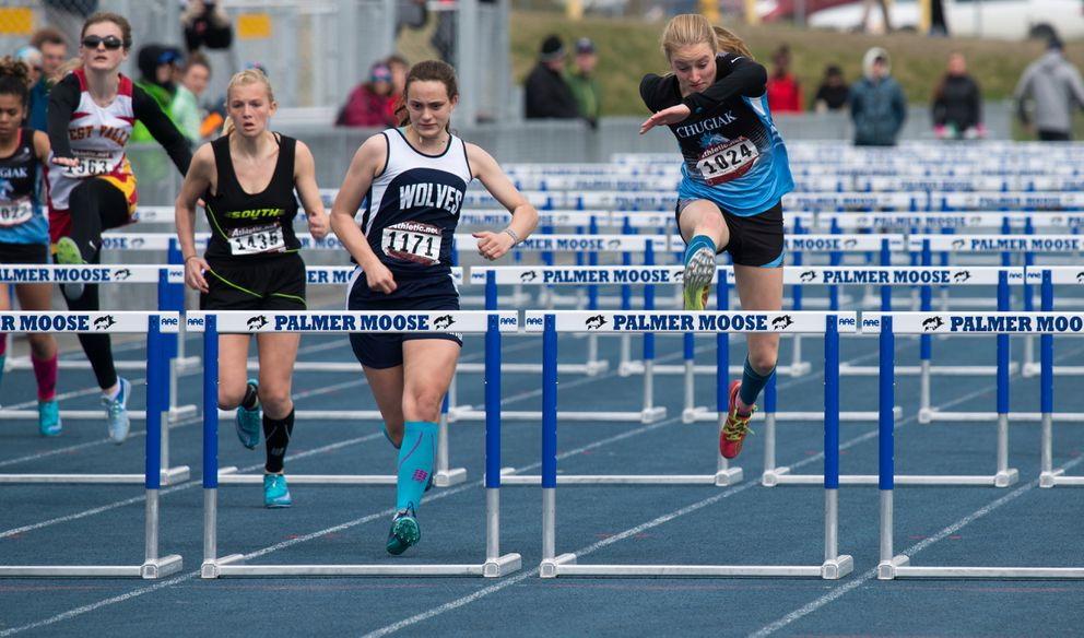 Chugiak's Brooklynn Gould (right) clears the final hurdle in the girls 100-meter hurdle race. (Photo by Stephen Nowers)