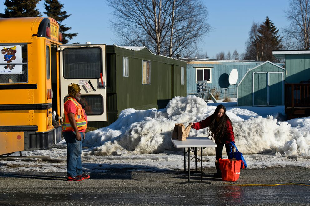 Bus driver Leonard Collins, left, watches as lunches are picked up at the day's first stop. (Marc Lester / ADN)