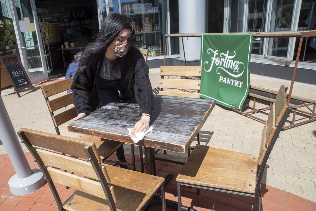 An employee at Fortina restaurant disinfects an outdoor table in preparation for the opening of outdoor dining, Wednesday, May 20, 2020, in Stamford, Conn. Restaurants can begin offering service in outdoor dining areas Wednesday as part of the first phase of Connecticut's statewide reopening, including in hard-hit Fairfield County on the New York state line. (AP Photo/Mary Altaffer)
