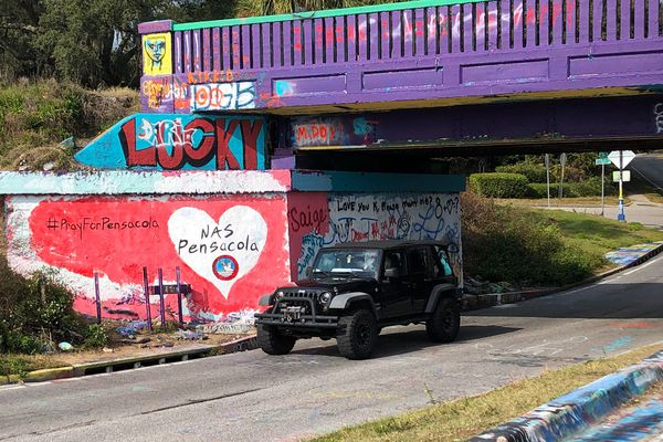 A vehicle drives by a tribute to victims of the Naval Air Station Pensacola that was freshly painted on what's known as Graffiti Bridge in downtown Pensacola, Fla., on Saturday, Dec. 7, 2019. A US official says the Saudi student who fatally shot three people at the Florida naval base had hosted a dinner party earlier in the week to watch videos of mass shootings. The official spoke on condition of anonymity after being briefed by federal investigators.The official says a second Saudi student was recording outside the building at the Naval Air Station Pensacola on Friday while the shooting was happening inside. The official also says 10 Saudi students are being held at the base and that several others are unaccounted for. (AP Photo/Brendan Farrington)