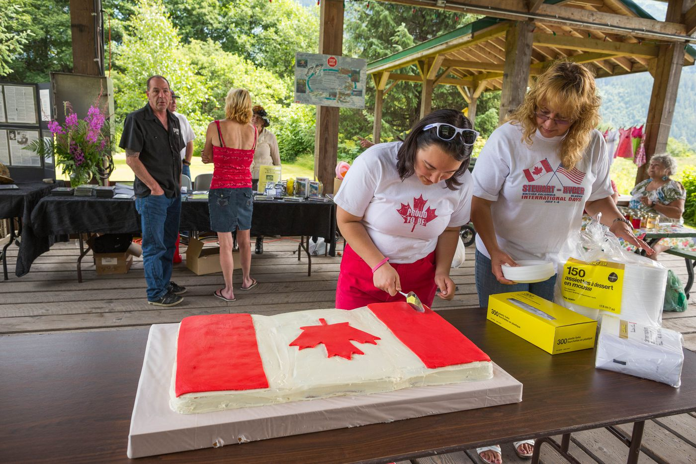 """Former mayor of Stewart, British Columbia Angela Brand Danuser, right, and Jorja Danuser cut the Canada Day cake in Stewart on July 1, 2015. """"We consider ourselves one community,"""" said Brand Danuser. """"We do everything together, and everything that Stewart does, we promote it as Stewart and Hyder."""""""