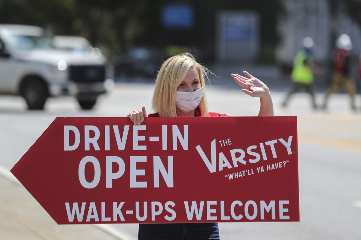 Ashley Weiser, the great granddaughter of The Varsity founder Frank Gordy, wearing a face mask holds a sign Tuesday, April 28, 2020 at 61 North Ave NW in downtown Atlanta. The restaurant is assuring customers they are following the guidelines from the CDC and Governor's office during the COVID-19 pandemic. (John Spink/Atlanta Journal-Constitution via AP)
