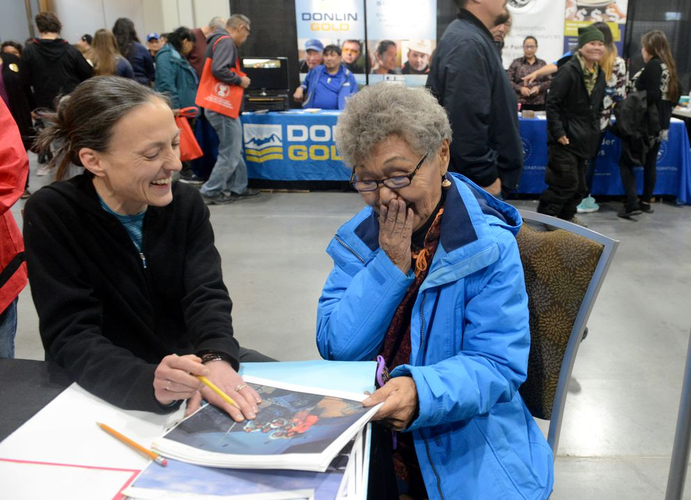 Anchorage Museum archivist Sara Piasecki works with Gemma Gaudio on identifying peoples in photographs from Hooper Bay, AK at the Anchorage Museum booth at AFN. (Bob Hallinen / ADN)