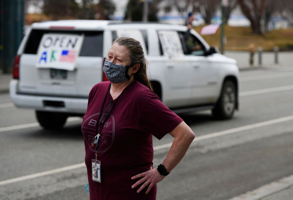 """Ruth Kvernplassen watches protesting vehicles pass on 6th Avenue in front of City Hall on April 22, 2020. Kvernplassen said she supports the mayor's approach to a phased reopening of the city. """"I think that it's divisive and that it's loud,"""" she said of the protest. """"I think what they're asking for is too soon."""" (Marc Lester / ADN)"""
