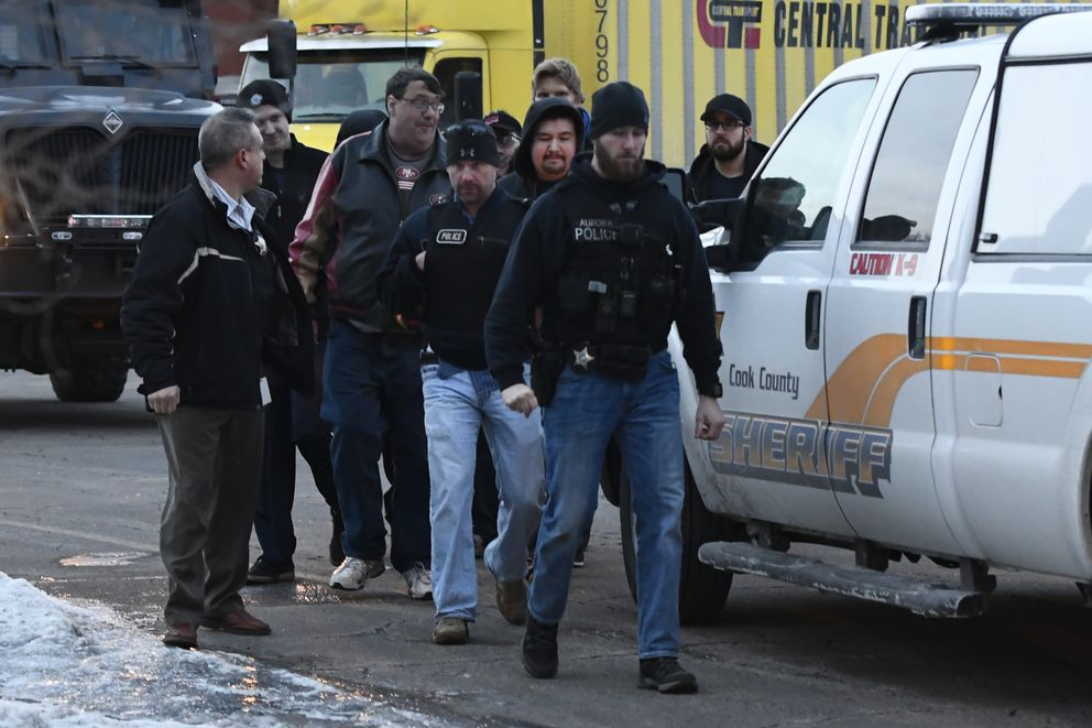 Employees are escorted from the scene of a shooting at a manufacturing company, Friday, Feb. 15, 2019, in Aurora, Ill, that police said left several people dead and several police officers wounded. (AP Photo/Matt Marton)