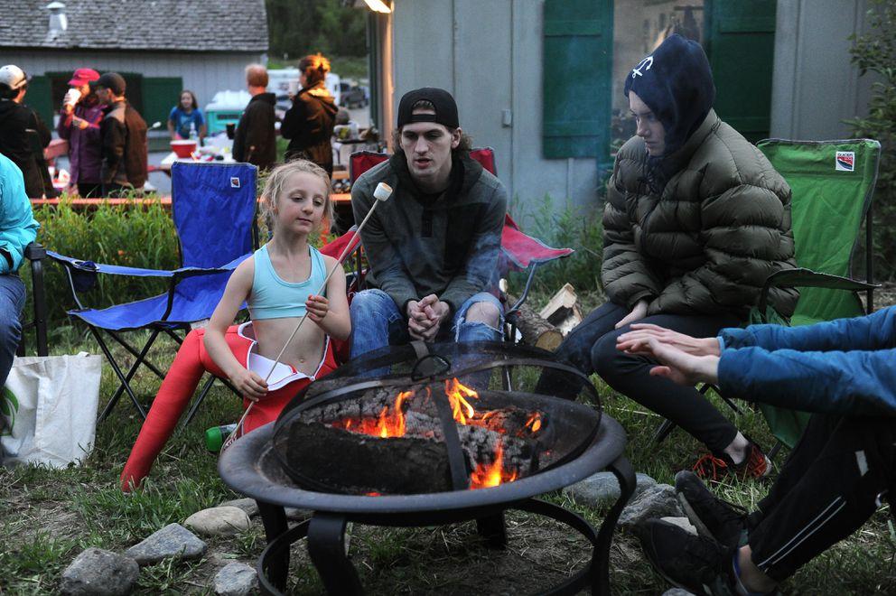Neve Cogdon roasts a marshmallow during the Midnight Sun Ski Jump-A-Thon. (Bob Hallinen / ADN)