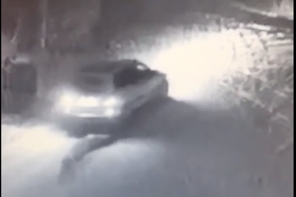 A white Volvo station wagon is seen pulling a rolled piece of carpeting onto College Road near Aurora Subdivision in this still image from video provided by Alaska State Troopers.