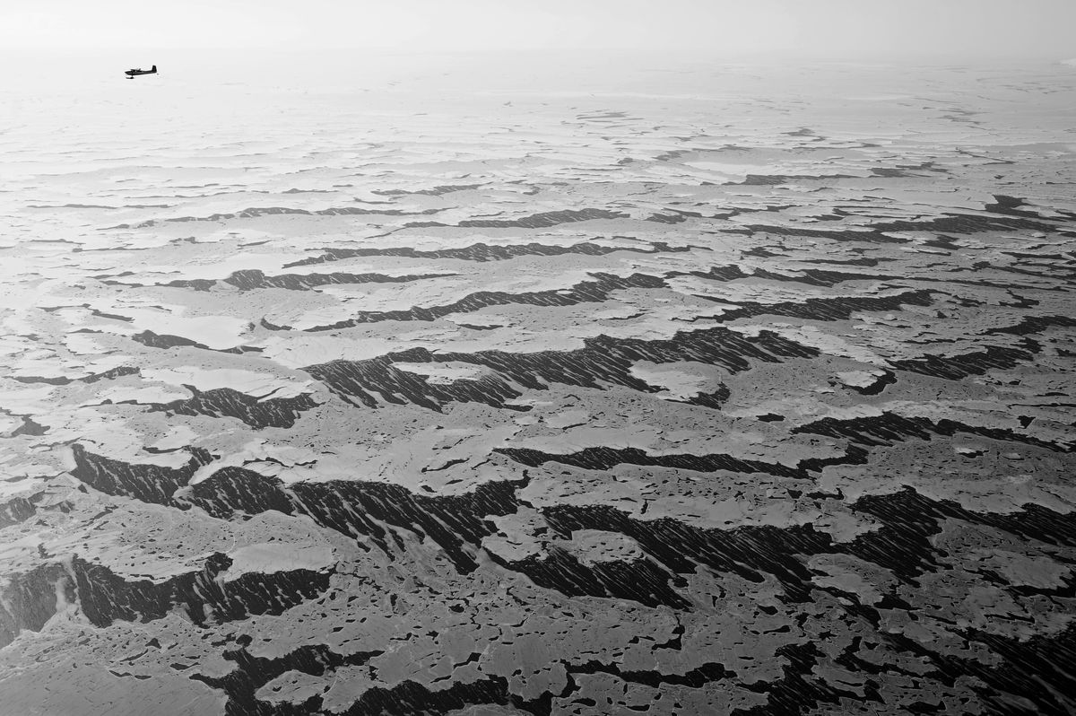 An airplane flies over a pattern of windblown ice and snow near the coast of eastern Norton Sound. (Marc Lester/ADN file)