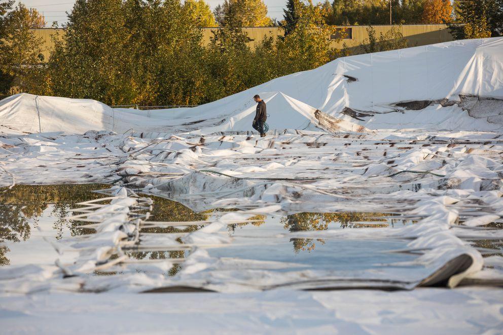 Davis Constructors employee Jason Meisler walks amid rain-filled remains of The Dome Friday, Sept. 15, 2017. (Loren Holmes / Alaska Dispatch News)
