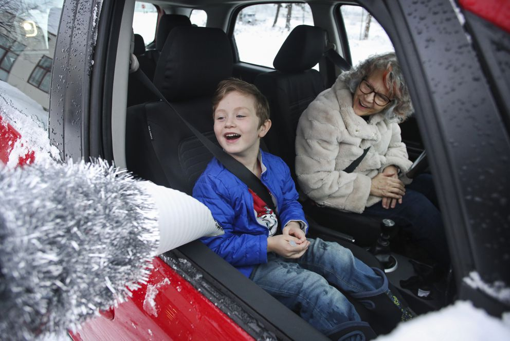 Jackson Rhinehart, 5, and his grandmother, Jean Stanley, watch as a candy cane slides out of a chute and into his lap. (Emily Mesner / ADN)