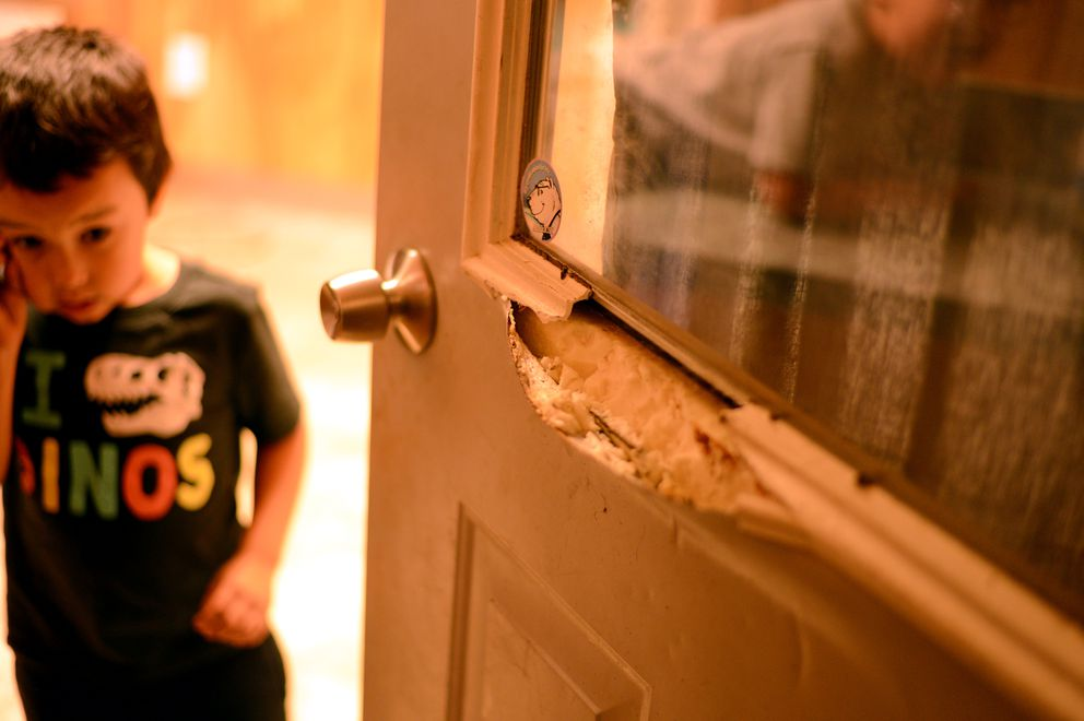 Five-year-old Aaron Lott is seen on Tuesday, Aug. 4, 2020 next to a door broken by a black bear Friday night at his family home. (James Brooks / ADN)