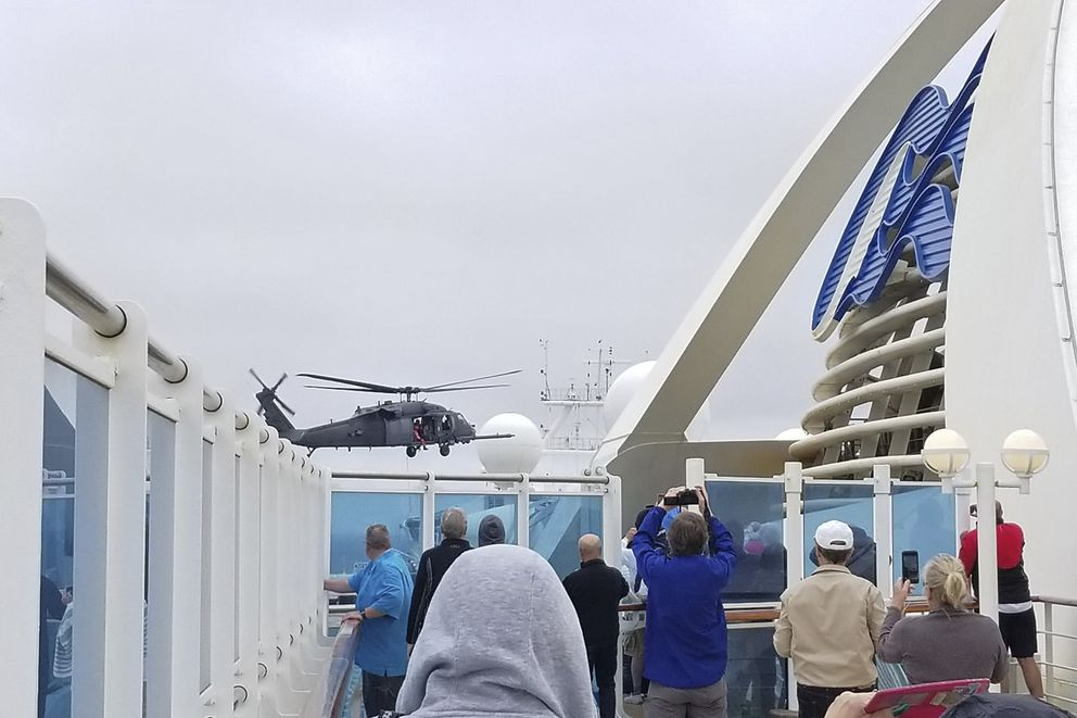 CORRECTS FROM COAST GUARD TO NATIONAL GUARD HELICOPTER- In this photo provided by Michele Smith, passengers look on as a National Guard helicopter hovers above the Grand Princess cruise ship Thursday, March 5, 2020, off the California coast. Scrambling to keep the coronavirus at bay, officials ordered a cruise ship with about 3,500 people aboard to stay back from the California coast Thursday until passengers and crew can be tested, after a traveler from its previous voyage died of the disease and at least two others became infected. A Coast Guard helicopter lowered test kits onto the 951-foot (290-meter) Grand Princess by rope as the vessel lay at anchor off Northern California, and authorities said the results would be available on Friday. Princess Cruise Lines said fewer than 100 people aboard had been identified for testing. (Michele Smith via AP)