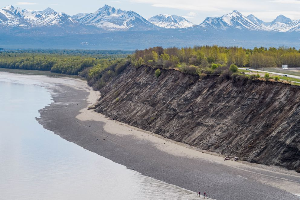 People walk along the beach at Point Woronzof on Tuesday, May 14, 2019. The bluff has been eroding for many years and is encroaching on the popular Tony Knowles Coastal Trail and nearby road. (Loren Holmes / ADN)