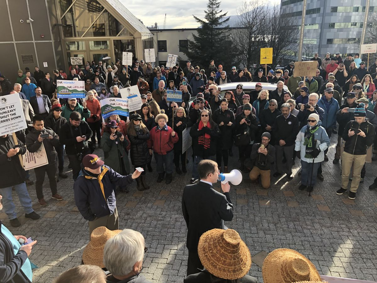 Sen. Jesse Kiehl, D-Juneau, speaks into a megaphone during a protest in front of the Alaska State Capitol on Tuesday, Feb. 11, 2020. Protesters were urging greater ferry funding. (James Brooks / ADN)