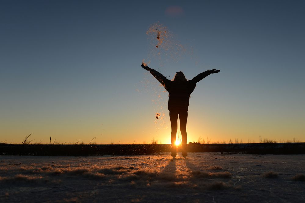 Abigail Thomas throws cattail fluff into the air as the sunsets on the ice at Potter Marsh in south Anchorage, AK on Sunday, Nov. 4, 2018. (Bob Hallinen / ADN)