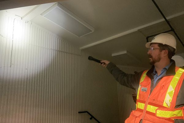 David Stierwalt, an engineer with Reid Middleton, points to a crack where a stairwell partially separated from the wall at Gruening Middle School during a walk-through of Gruening Middle School held for community members on Thursday, Dec. 19, 2019. School district officials and engineers conducted a tour of the building to show areas in need of repair and detail upgrades that will be made to the facility, which was damaged in the Nov. 30, 2018 earthquake. (Matt Tunseth / ADN)