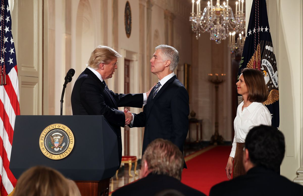 President Donald Trump shakes hands with Judge Neil Gorsuch, his nominee for the vacant Supreme Court seat, at the White Houseon Tuesday. Gorsuch's wife, Louise, is at right. (Stephen Crowley / The New York Times)