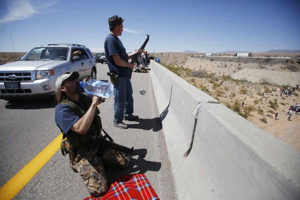 FILE PHOTO: Scott Drexler (L), and Steve Stewart from Idaho stand watch on a bridge as protesters gather by the Bureau of Land Management's base camp, where cattle that were seized from rancher Cliven Bundy are being held, near Bunkerville, Nevada April 12, 2014. REUTERS/Jim Urquhart