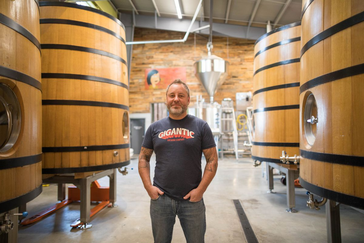 Anchorage Brewing owner Gabe Fletcher at his South Anchorage brewery on Thursday. Behind him are fouders, French oak fermentation barrels more commonly used for making wine. (Loren Holmes / Alaska Dispatch News)