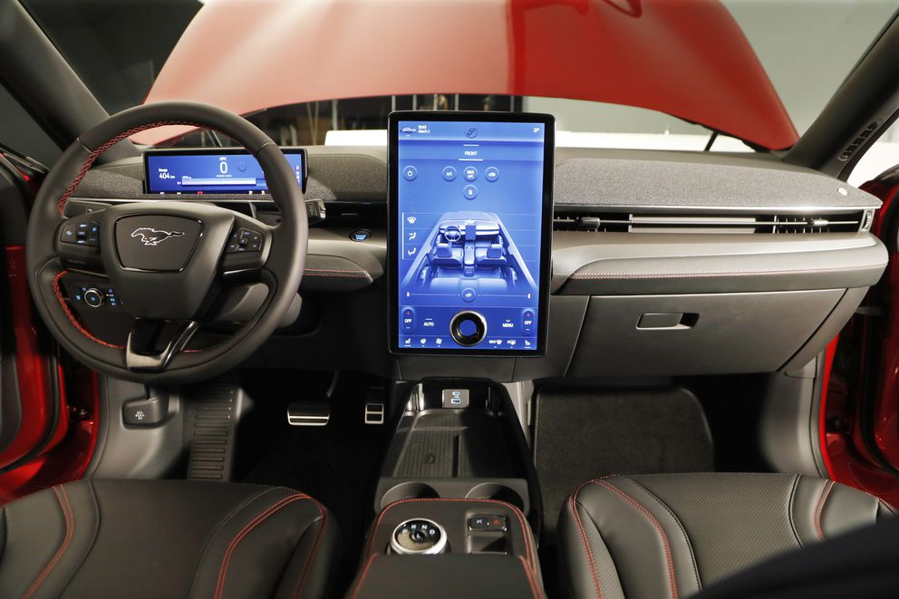 This Wednesday, Oct. 30, 2019 photo, shows the interior of the new Ford Mustang Mach-E SUV in Warren, Mich. Ford is hoping to score big with the electric SUV for daily drivers that sort of looks like a Mustang performance car. The new SUV, to be unveiled just ahead of the Los Angeles Auto Show press days, should have range of up to 300 miles. It's one of dozens of electric vehicles coming globally by 2022. Automakers are eyeing what they think will be a growing market in the years to come. (AP Photo/Carlos Osorio)