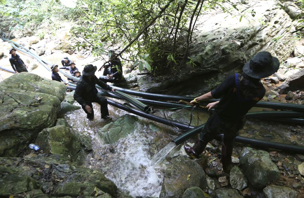 Thai soldiers drag water pipes to bypass water from mountain not get back to inside a cave where 12 boys and their soccer coach have been trapped since June 23, in Mae Sai, Chiang Rai province, in northern Thailand Saturday, July 7, 2018. Thai authorities are racing to pump out water from the flooded cave before more rains are forecast to hit the northern region. (AP Photo/Sakchai Lalit)