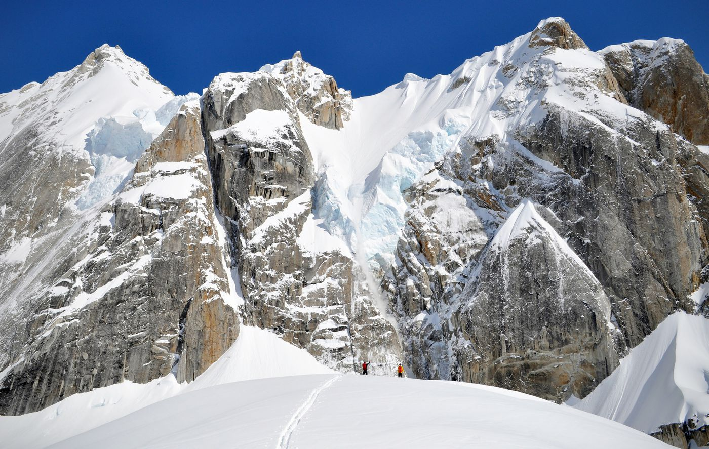 Matt Cress, left, and Steven Claggett watch a natural avalanche come down from the seracs beneath the ridge line that links Bear Tooth and Eye Tooth. (Vicky Ho / ADN)