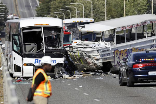 An emergency official stands near a charter bus, left, and a