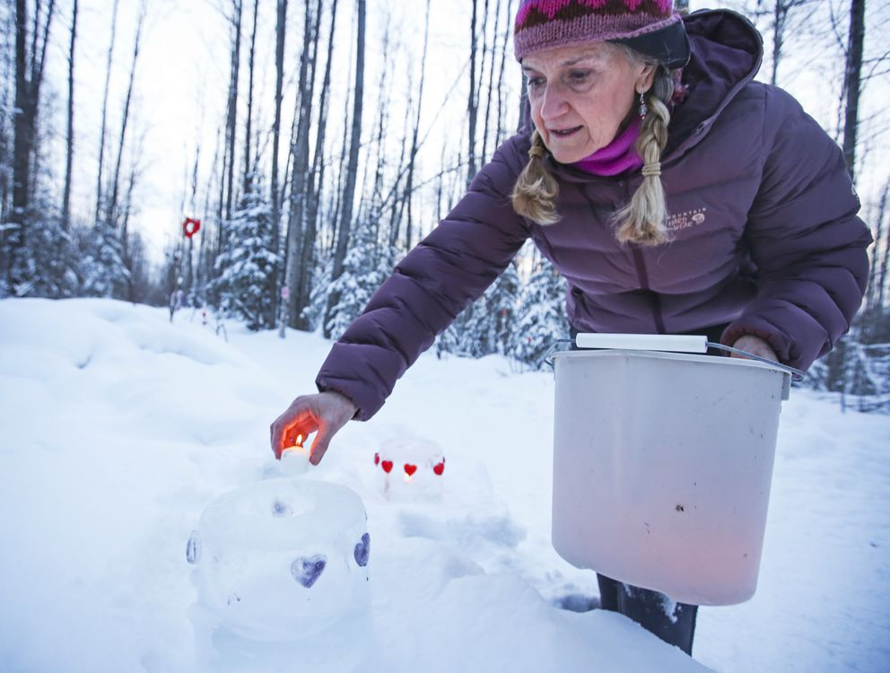 Colette Ravinet places a lit candle into an ice luminaria. (Emily Mesner / ADN)
