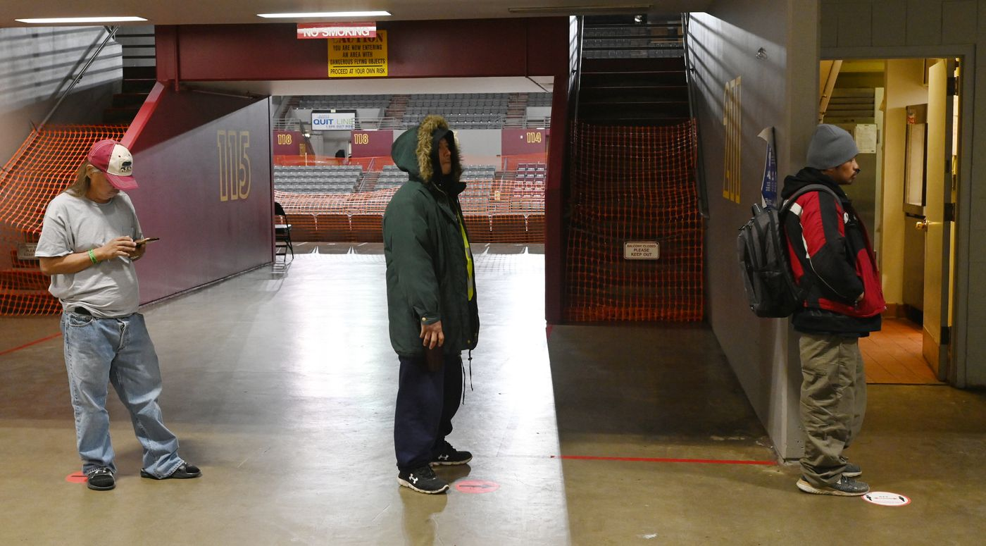 Clients stand on dots marking proper social distance spacing while waiting for sack lunches to be distributed at the Bean's Cafe emergency shelter inside the Sullivan Arena during the COVID-19 pandemic on Wednesday, April 29, 2020. (Bill Roth / ADN)