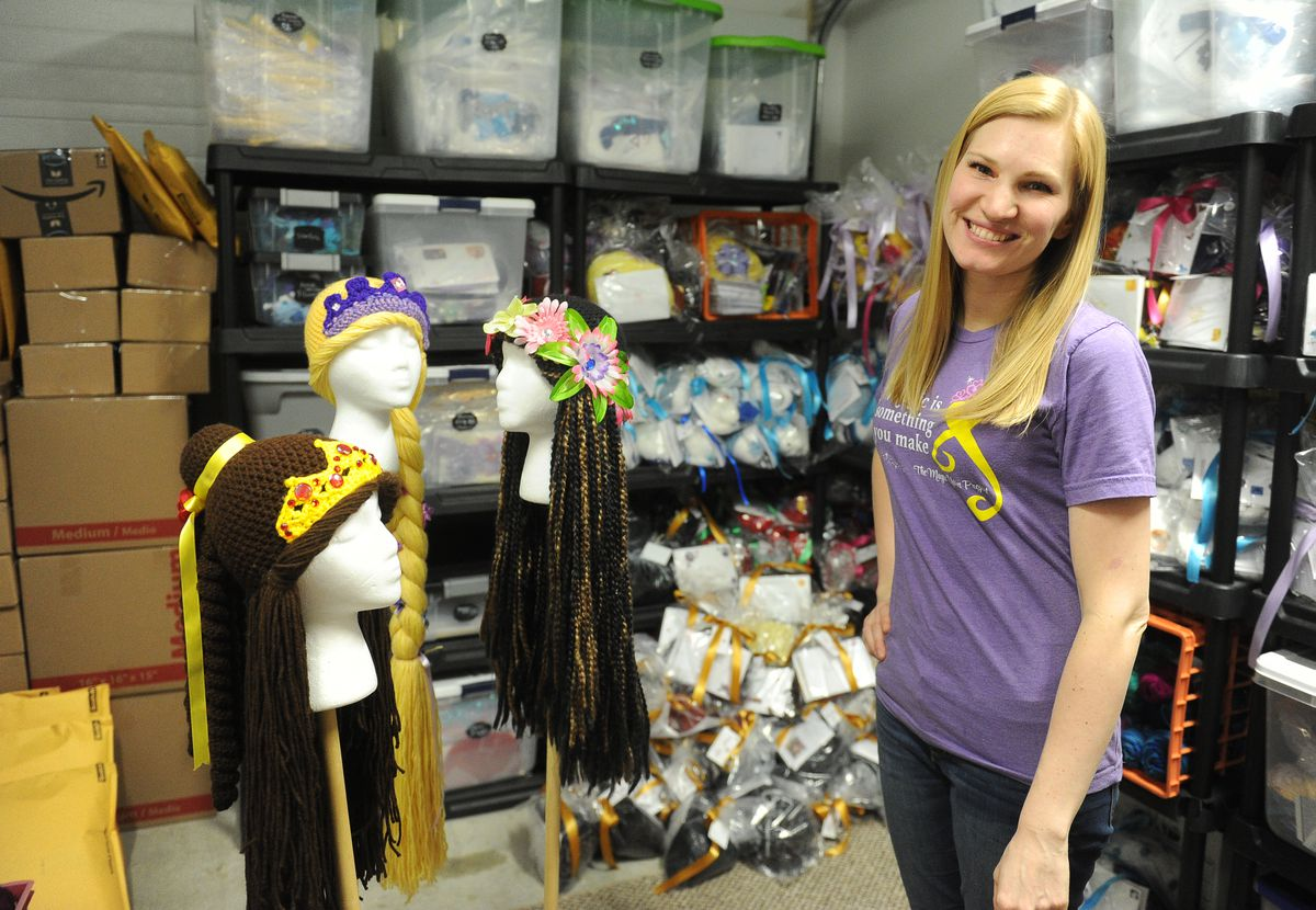 Holly Christensen poses with some of the wigs made by The Magic Yarn Project in Palmer. (Bob Hallinen / ADN)