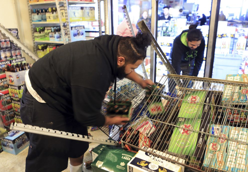Adriel Matavo, left, and Aisoli Lealasola work in a walk-in cooler to clean up fallen cases of beer at a liquor store, Value Liquor, after an earthquake on Friday, Nov. 30, 2018, in Anchorage, Alaska. Owner Mary Funner says beer, wine and other bottled alcohol was strewn throughout store aisles after the quake. She considered closing Friday until customers began lining up. They were allowed to come in in small groups. 'We're still in business, but we're only open only a little bit at a time, ' she said. (AP Photo/Dan Joling)