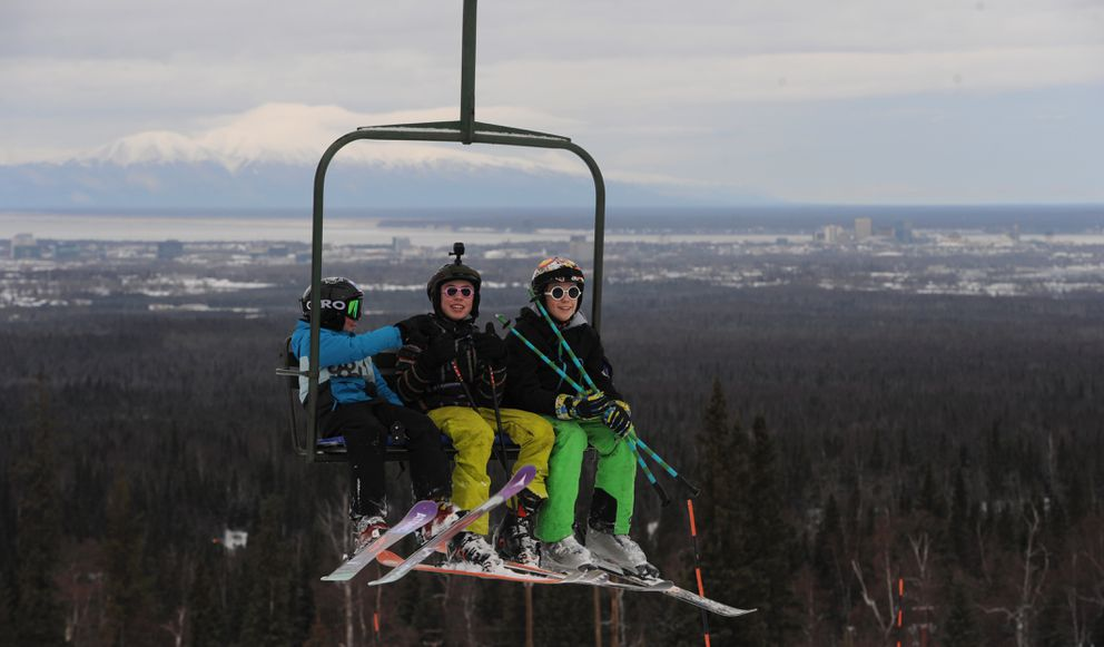 Skiers ride the triple chairlift at Hilltop Ski Area on Sunday with a view of Anchorage and Mount Susitna in the distance. (Bill Roth / ADN)