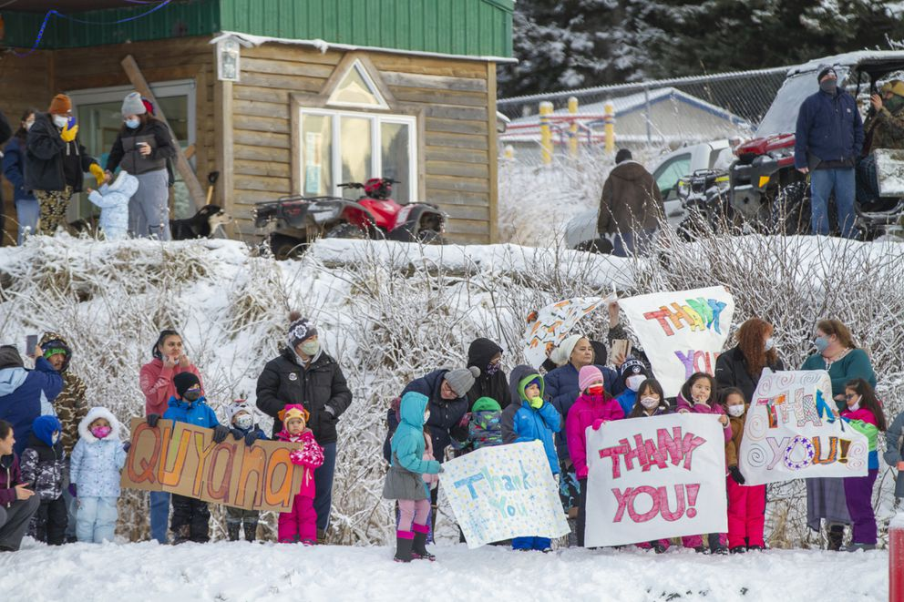 Residents of the village of Nanwalek, on Alaska's Kenai Peninsula, greet guardsmen who delivered presents in a CH-47 Chinook helicopter from 1st Battalion, 207th Aviation Regiment, during Operation Santa, Dec. 11, 2020. (Edward Eagerton/U.S. Army National Guard via AP)