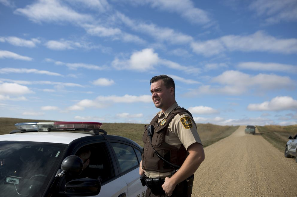 Deputy Jon Moll of the Morton County Sheriff's Office visits officers stopped along North Dakota Highway 1806, near Cannon Ball, N.D., where many have gathered to protest the Dakota Access pipeline, on Oct. 8. (Kristina Barker / The New York Times)