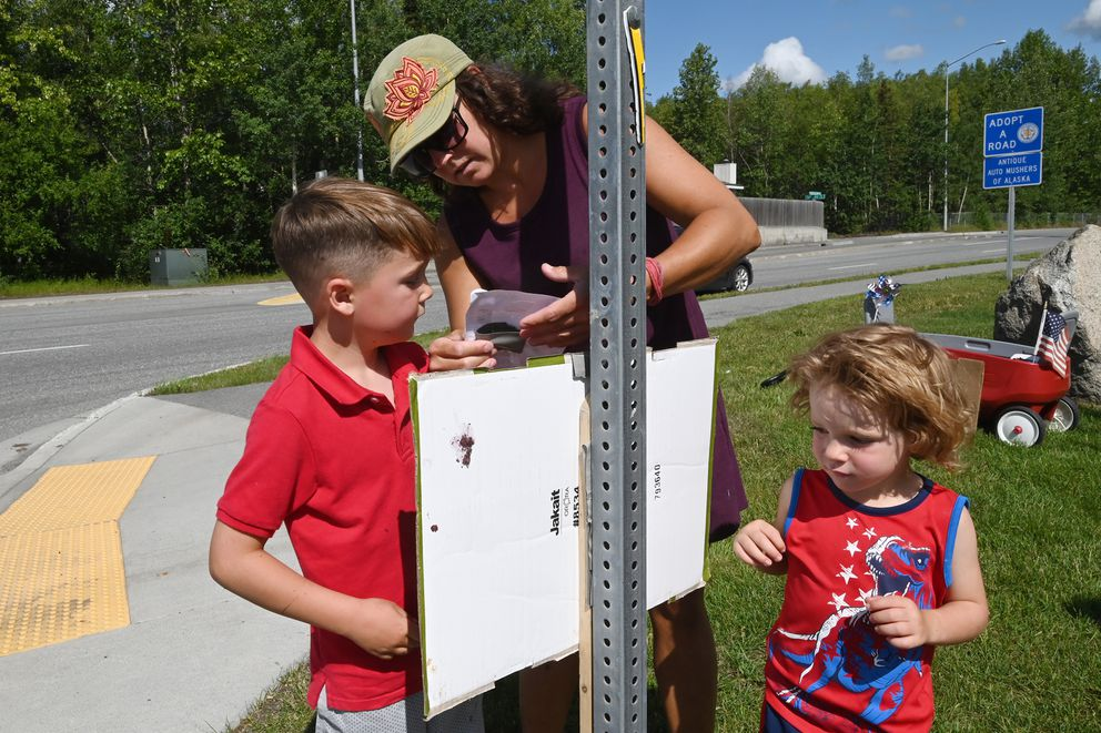 Renee Lajuett posted signs outside the Anchorage School District building on Tuesday, July 21, 2020, with her children Tanner, 7, and Xander, 3, showing their support for opening schools five days a week. (Bill Roth / ADN)