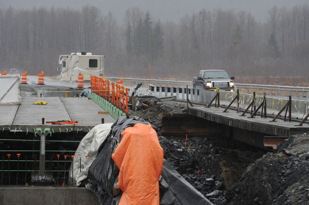 Motorists traveling on the Seward Highway take a detour over a temporary bridge during construction of a new bridge at Virgin Creek south of Girdwood on Thursday, April 11, 2019. (Bill Roth / ADN)