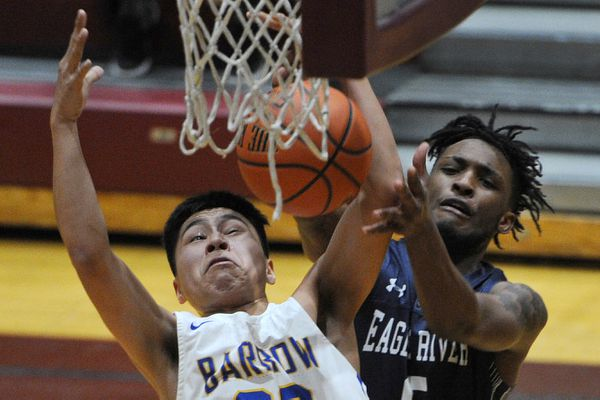 Barrow junior forward Isiah Mongoyak and Eagle River senior forward Ja'Corrie Benoit battle for control of the ball during the Whalers' 76-73 OT victory over the Wolves during the opening game of the Alaska Prep Shootout at Dimond High on Thursday, Jan. 10, 2019.