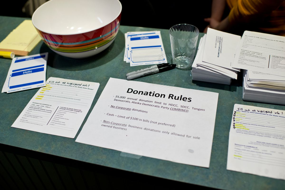 Signs at the front table of a Democratic fundraiser spell out donation rules at the Juneau-Douglas City Museum. Democrats and Republicans both held fundraising events on the night before the legislative session began in Juneau on Jan. 16. (Marc Lester / Alaska Dispatch News)