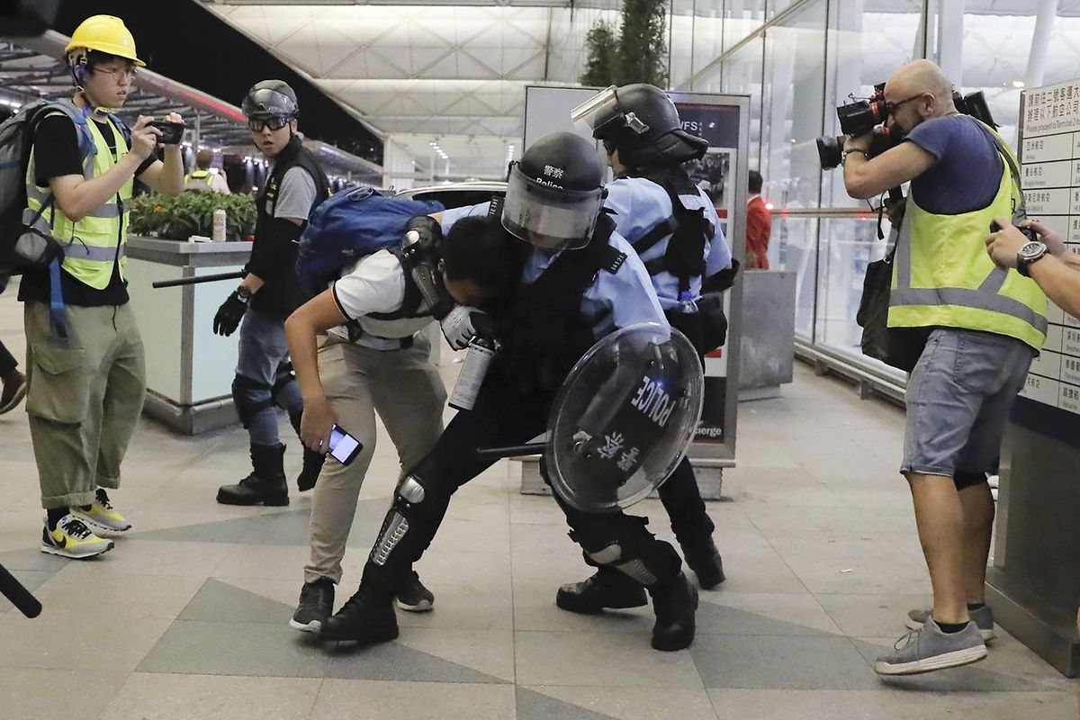 Policemen in riot gears arrest a protester during a demonstration at the Airport in Hong Kong, Tuesday, Aug. 13, 2019. Chaos has broken out at Hong Kong's airport as riot police moved into the terminal to confront protesters who shut down operations at the busy transport hub for two straight days. (AP Photo/Kin Cheung)