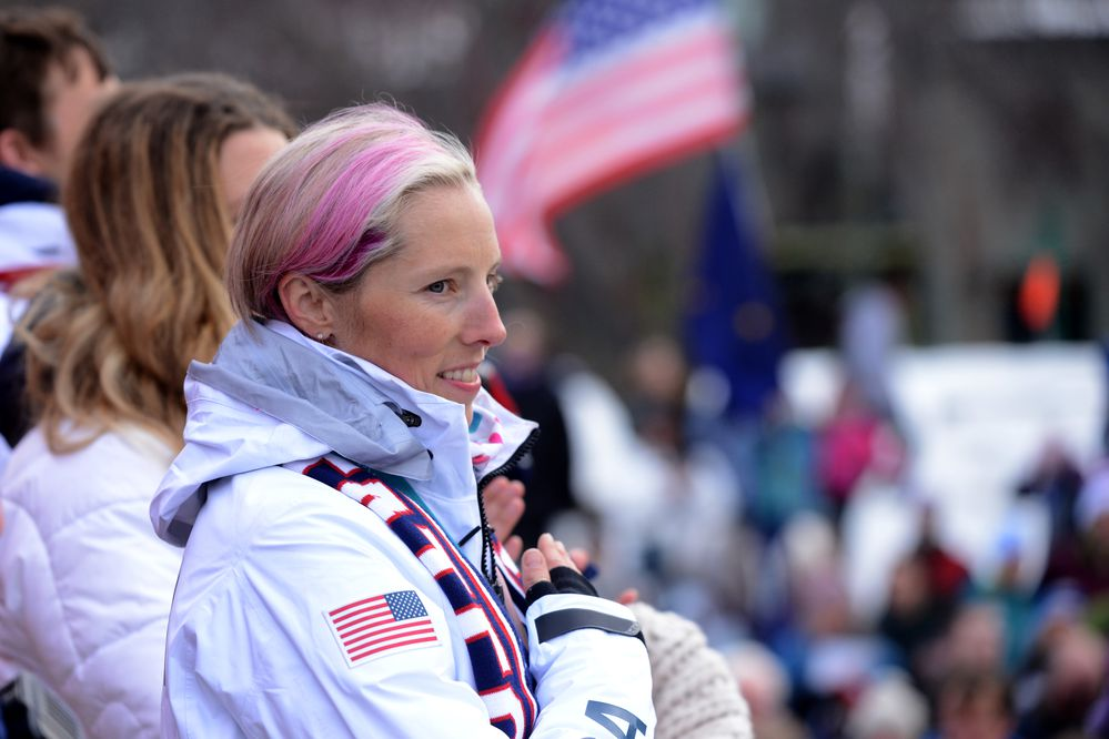 Cross-country ski Olympian Kikkan Randall and other Olympians listen to the East High band play the National Anthem in Town Square Park in Anchorage on Wednesday April 4, 2018. All of the Alaska Olympians from the winter and summer games and the Paralympics were honored during the celebration. (Bob Hallinen / ADN)