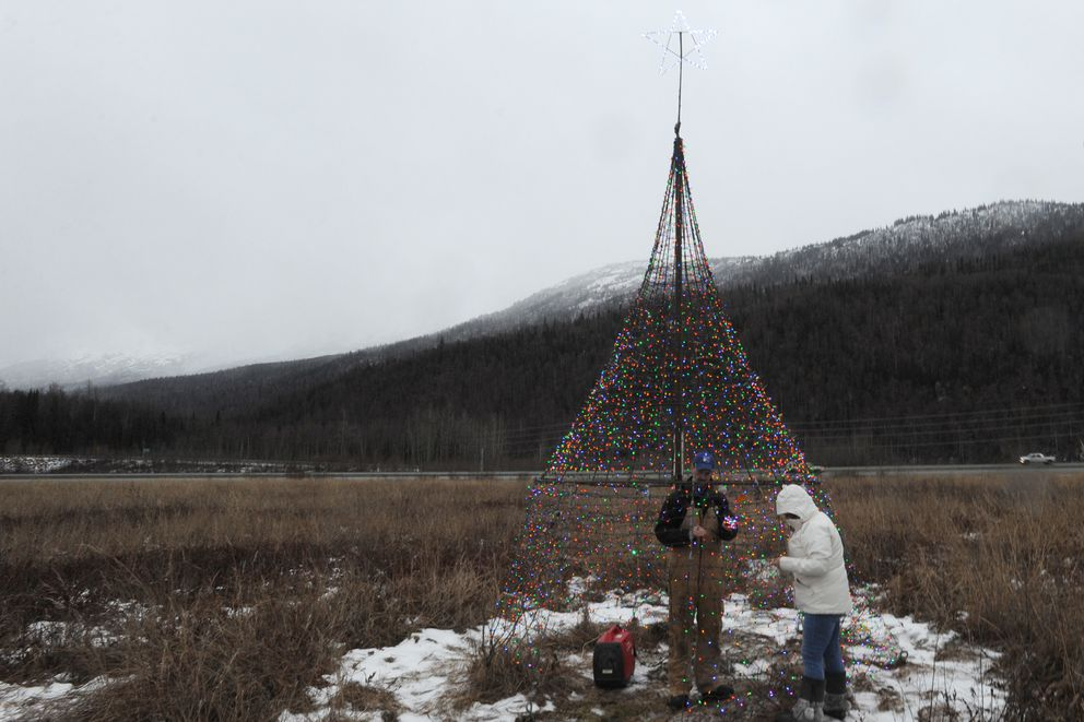 Jason Tolstrup and Kaye Mack checks the lights on the replacement Christmas tree along the Glenn. (Bill Roth / ADN)
