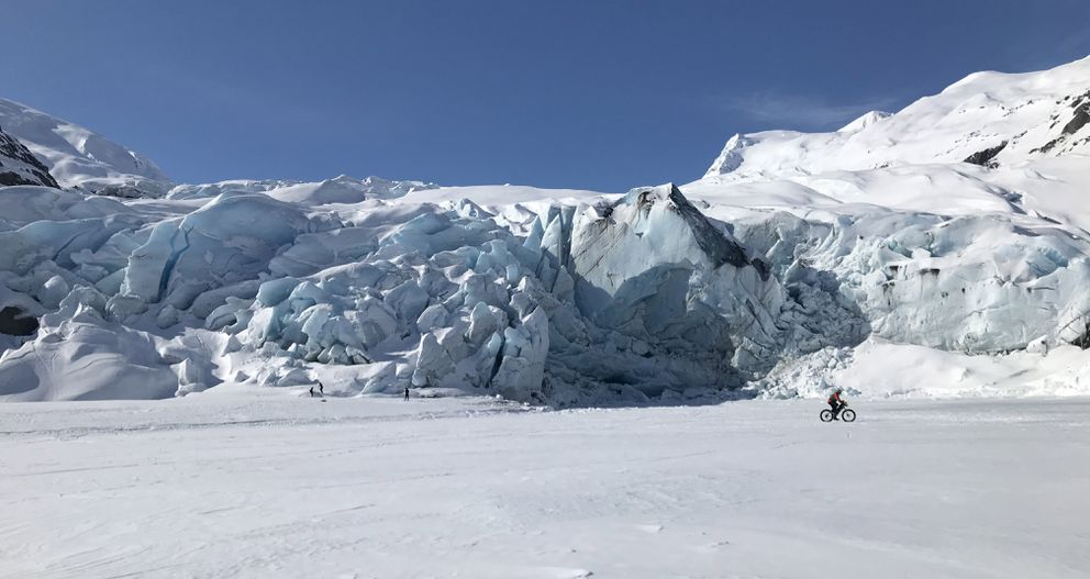 A biker pedals past a face of Portage Glacier on Friday, April 10, 2020. A large portion of this face of the glacier calved Saturday, April 11, 2020. Fortunately, no one was close enough to be injured. (Anne Raup / ADN)