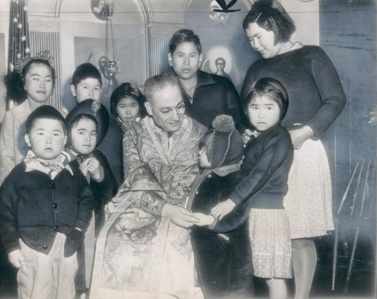 Attu children in Tacoma, Wash., following their release from Japan at the end of World War II. The girl in the hat touching the priest's hand is Elizabeth Golodoff Kudrin, now one of two survivors of the internment. (Photo from Betty Bendixon, courtesy Rachel Mason)