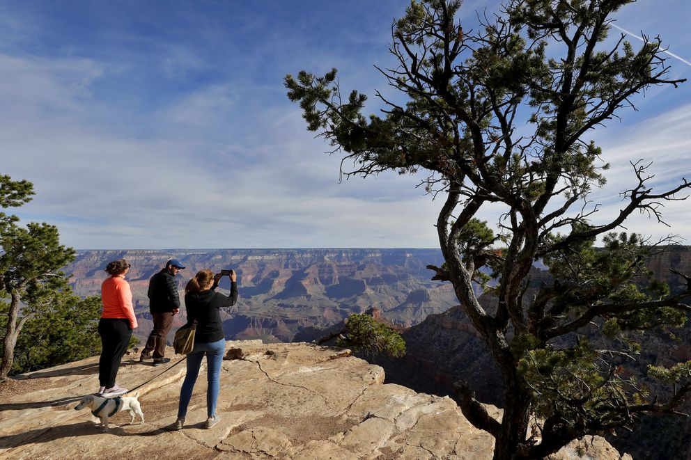 In this May 15, 2020 file photo, Tanya Wyler takes a photograph as Matthias Zather and Ines Zather, all of Switzerland, gather at the Grand Canyon in Grand Canyon, Ariz. (AP Photo/Matt York, File)