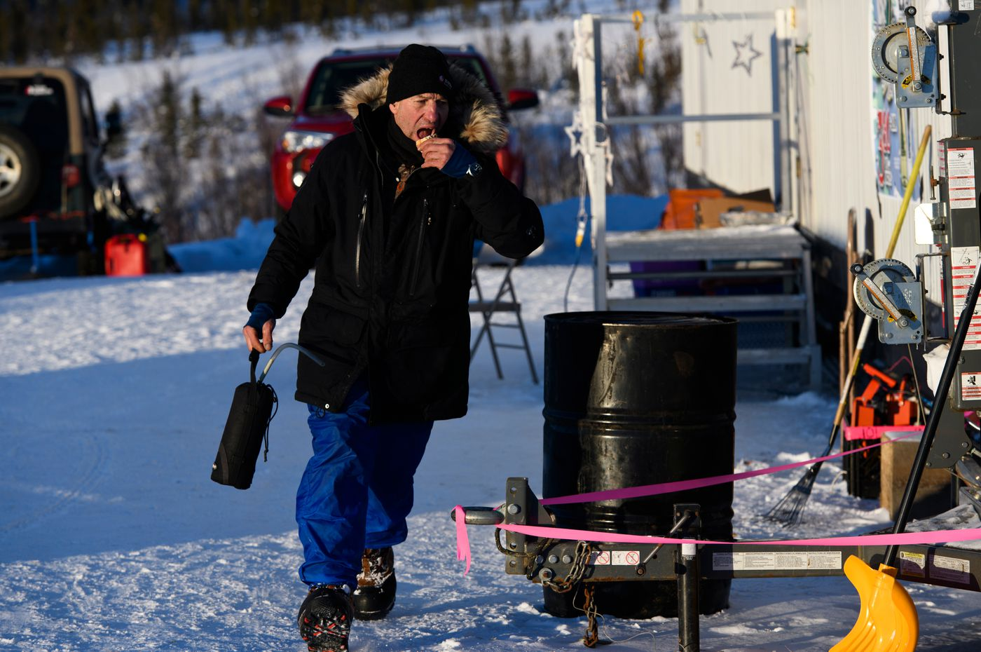 Hans Gatt runs back to his sled after filling his bottle and getting some food at the Mile 101 checkpoint. Yukon Quest International Sled Dog Race frontrunners passed checkpoints along the Steese Highway on February 10, 2019. (Marc Lester / ADN)