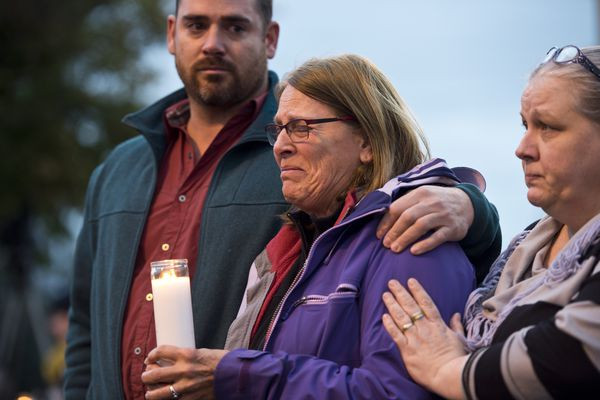 From left, Brian Montalbo and his mother Sylve Montalbo and hold candles at the vigil. About 40 people gathered on the Delaney Park Strip in downtown Anchorage on October 5, 2017 to remember the Alaskans killed in a recent mass shooting in Las Vegas. (Marc Lester / Alaska Dispatch News)