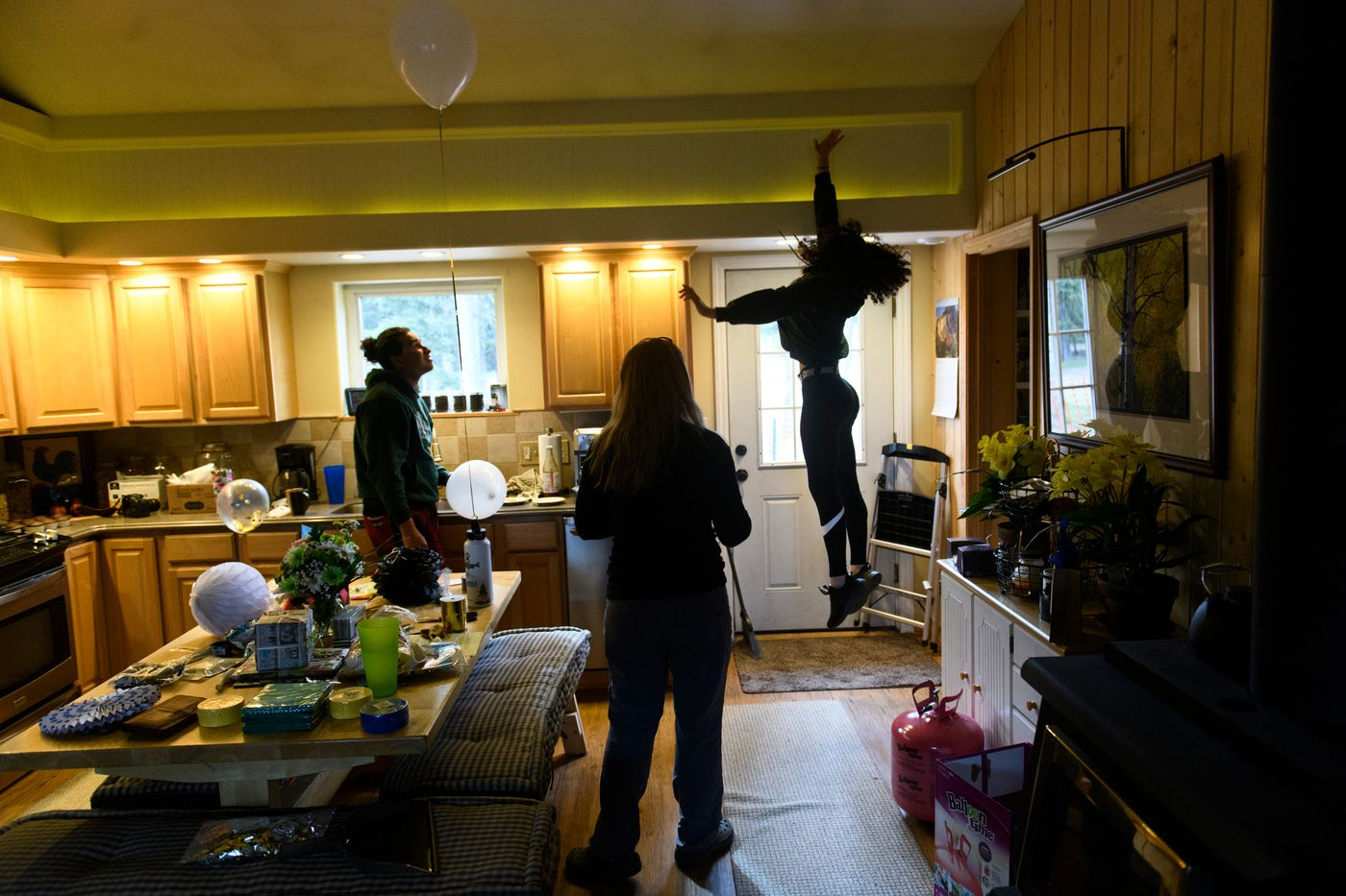 Hailey Williams jumps up to touch the ceiling in her family's home in Delta Junction. Hailey's brother Cameron is at left and her mother Eileen is at center. (Marc Lester / ADN)