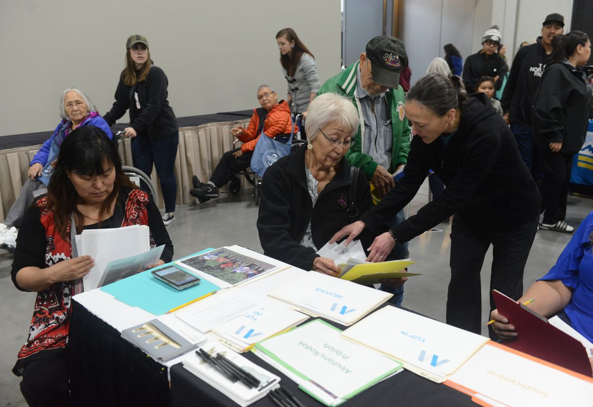 Alaska Federation of Natives Convention attendees look at photographs at the Anchorage Museum booth to try and identify people and places in them at the Dena'ina Center in Anchorage, AK on Thursday, Oct 18, 2018. The museum has been bringing recent photo donations to the convention for the past 6-years. (Bob Hallinen / ADN)