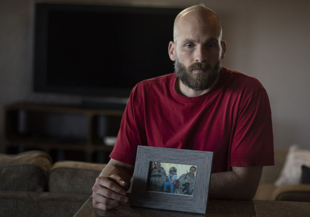 Michael Behenna holds a photo of his two comrades who were killed by a roadside bomb in Iraq in 2008. (Photo for The Washington Post by J Pat Carter)